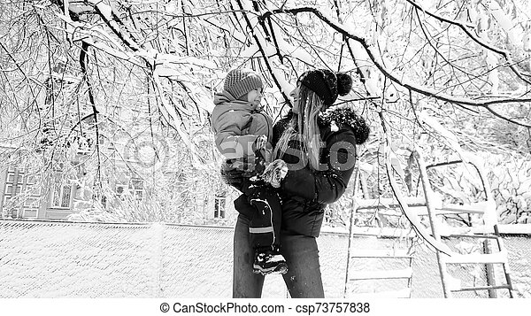 Monohrome portrait of mother with her cute son in jacket and hat playing with snow covered tree on the playground in the Park - csp73757838