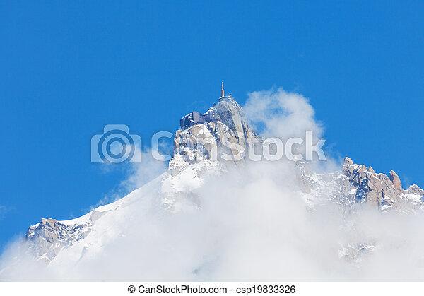 Mont Blanc peak in mist with blue sky - csp19833326
