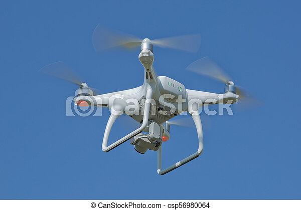 Un helicóptero con cámara digital de alta resolución en el cielo. Un dron blanco con cámara digital volando en el cielo sobre el dron de la montaña con cámara digital de alta resolución. - csp56980064