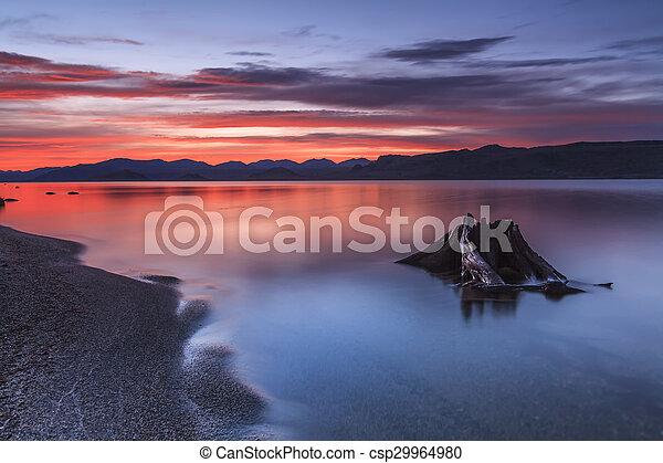 Un atardecer rojo increíble sobre un lago de montaña. - csp29964980