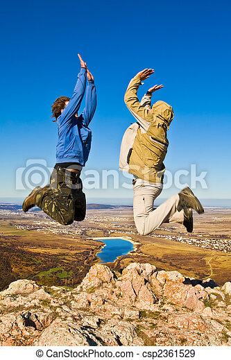 montaña, excursionistas, dos, saltar, cumbre, alegremente - csp2361529