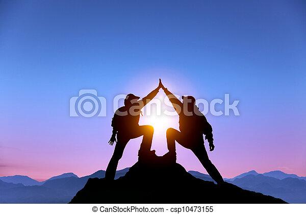 La Silueta de dos hombres con un gesto de éxito en la cima de la montaña - csp10473155
