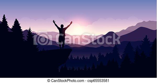 Un hombre feliz con brazos levantados está en lo alto de un acantilado en el paisaje de montaña al amanecer - csp65553581