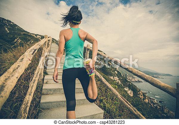 Una joven corredora de fitness estirando las piernas en el sendero de la montaña - csp43281223