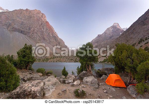 Una tienda naranja cerca del lago Blue Mountain al atardecer - csp25143817