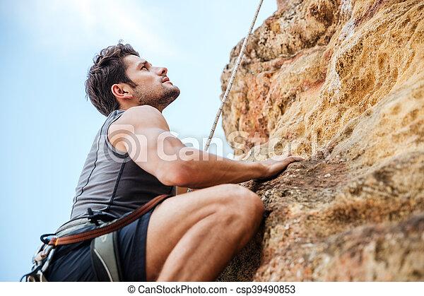 Un joven escalando una pared empinada en la montaña - csp39490853