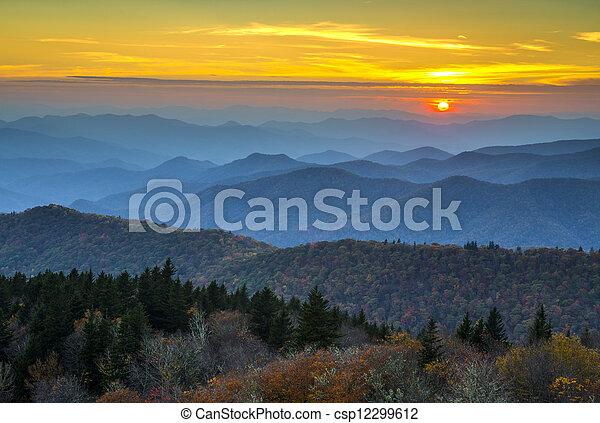 La puesta de sol de la cordillera azul sobre las capas de las montañas de aalaquía cubiertas de follaje de otoño y bruma azul - csp12299612
