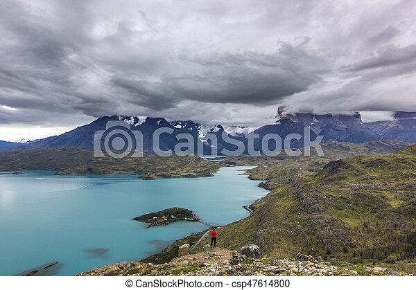 Chica con chaqueta roja en montañas de patagonia en neblina al amanecer cerca del lago azul - csp47614800