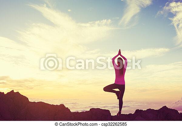 Mujer practicando yoga en las montañas al atardecer - csp32262585