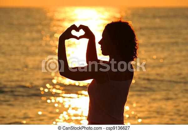 mooi, hart, vrouw, haar, jonge, zee, handen, maakt, ondergaande zon  - csp9136627