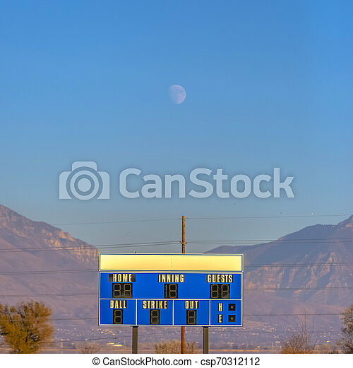 Moon hangs above the scoreboard of baseball field - csp70312112