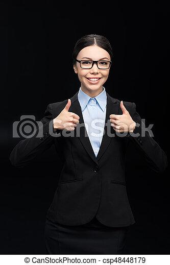 Mujer de negocios con traje negro mostrando pulgares aislados en negro - csp48448179