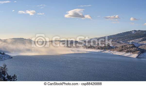 morning fog over mountain lake at foothills of Rocky Mountains - csp88426888