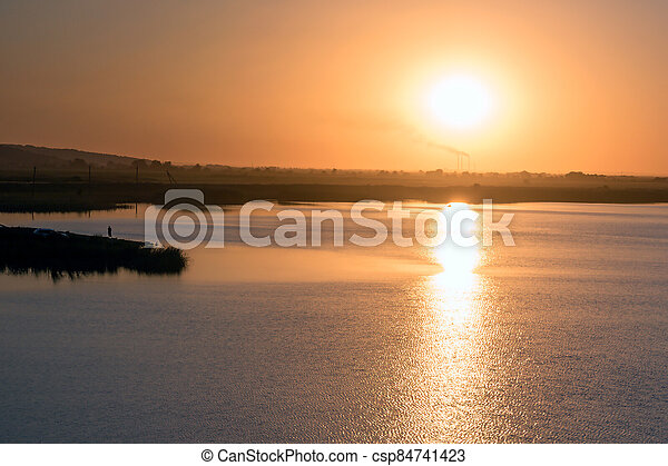 Morning view of the lake with a plant on the far background of sun rays - csp84741423
