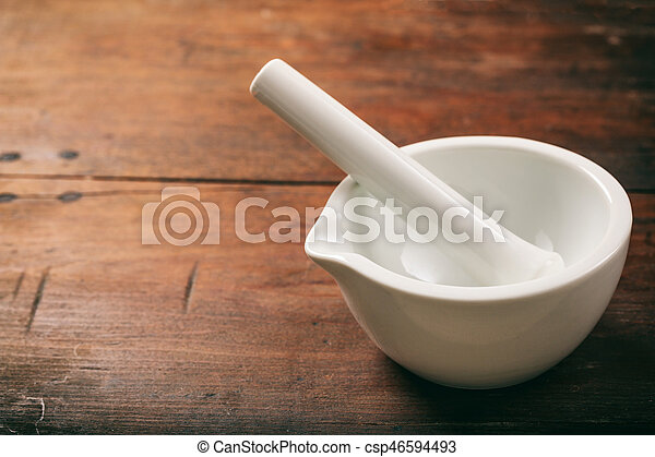 Mortar and pestle on wooden background - csp46594493