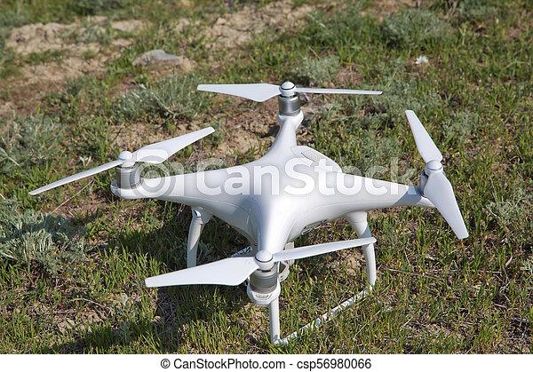 Un dron blanco con cámara digital volando en el cielo sobre el dron de la montaña con cámara digital de alta resolución. Drone con cámara en la hierba preparándose para volar. - csp56980066