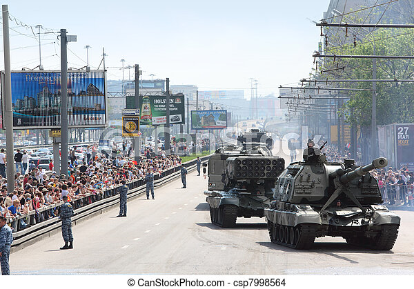 MOSCOW - MAY 9: People looks on weaponry and tank on road on parade in honor of Great Patriotic War victory on May 9, 2010 in Moscow, Russia. 160 military vehicle took part in parade - csp7998564