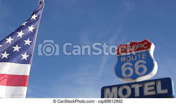 Motel retro sign on historic route 66 famous travel destination, vintage symbol of road trip in USA. Iconic lodging signboard in Arizona desert. Old-fashioned neon signage. National state flag waving - csp88812892