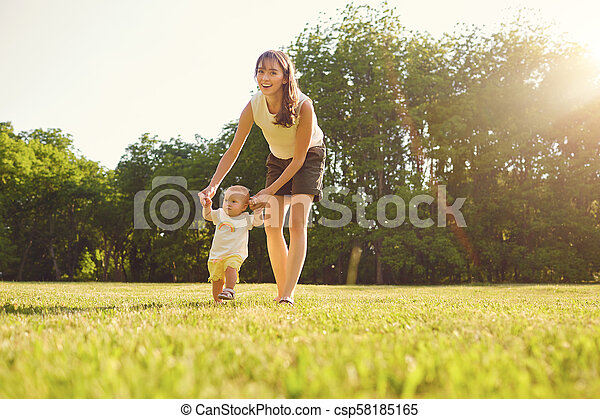 Mother and child are walking in the park at sunset . - csp58185165