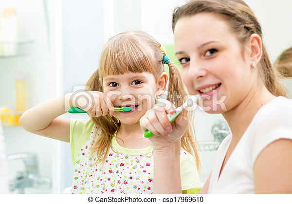 mother and child daughter brushing teeth in bathroom - csp17969610