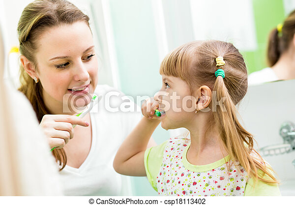 mother and child daughter brushing teeth in bathroom - csp18113402