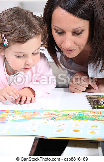 Mother and child looking at a book - csp8816189