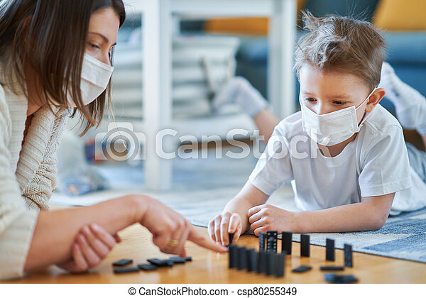 Mother and child playing together at home isolation during coronavirus pandemic - csp80255349
