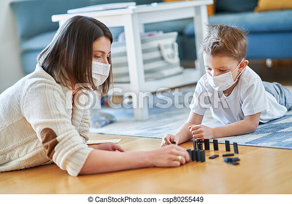 Mother and child playing together at home isolation during coronavirus pandemic - csp80255449
