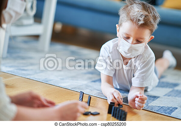 Mother and child playing together at home isolation during coronavirus pandemic - csp80255200