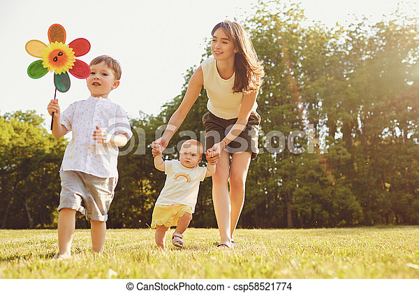 Mother and children are walking in the park at sunset. - csp58521774