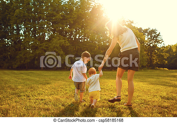 Mother and children are walking in the park at sunset . - csp58185168