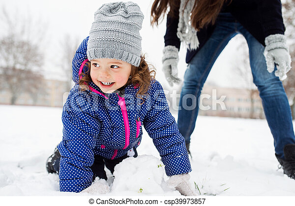 Mother and daughter building a snowman in winter nature - csp39973857