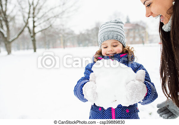Mother and daughter building a snowman in winter nature - csp39889830