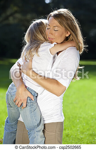 Mother and Daughter Cuddling In A Park - csp2502665