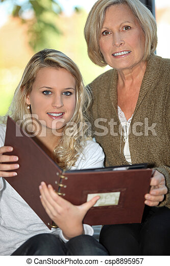 Mother and daughter looking through photo album - csp8895957