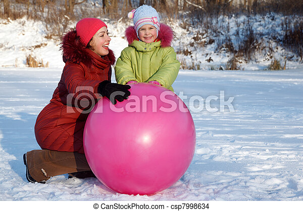 Mother and daughter playing outdoors in winter, with large inflatable ball. - csp7998634
