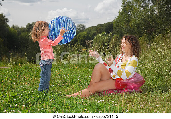 mother and daughter playing with ball in summer day at wood - csp5721145
