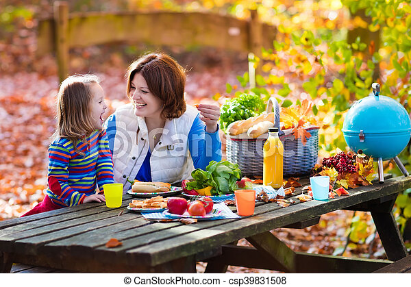 Mother and daughter set table for picnic in autumn - csp39831508