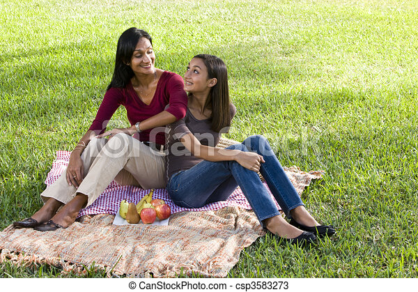 Mother and daughter sitting on picnic blanket - csp3583273
