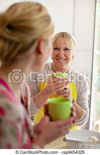 Mother and daughter talking, drinking coffee in kitchen - csp9454329