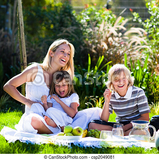 Mother and her children playing in a picnic in a park - csp2049081