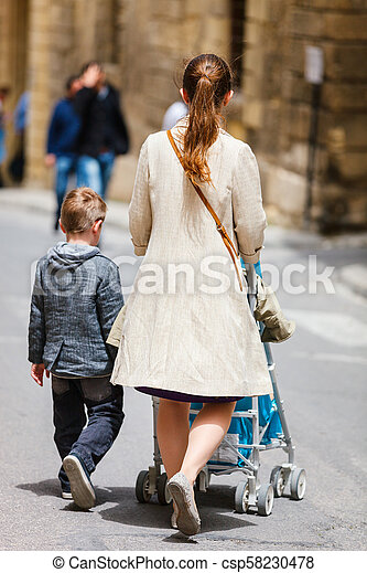 Mother and two kids walking in city center - csp58230478