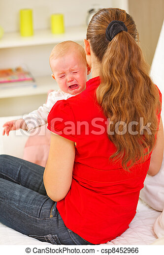 Mother calming crying baby - csp8452966