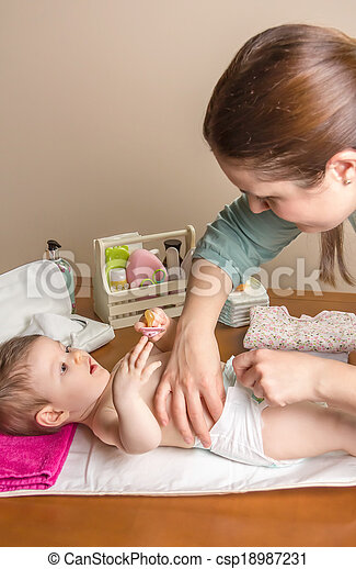 Mother changing diaper of adorable baby - csp18987231