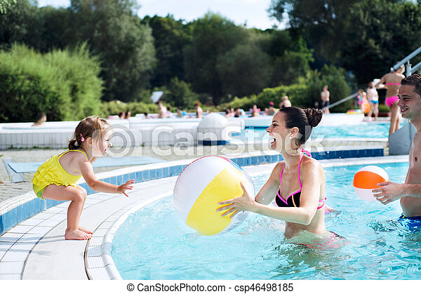 Mother, father and daughter in swimming pool. Sunny summer. - csp46498185
