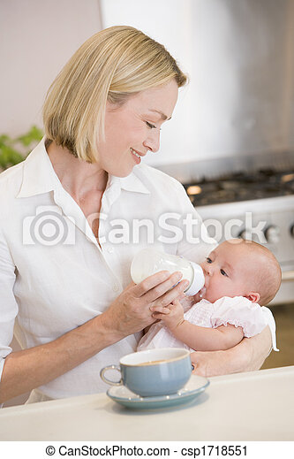 Mother feeding baby in kitchen with coffee smiling - csp1718551