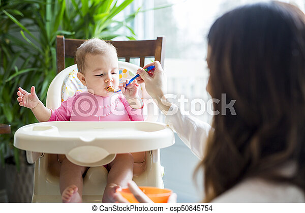 Mother feeding baby with spoon - csp50845754
