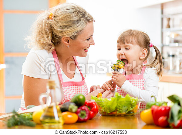 mother feeding kid daughter vegetables in kitchen - csp16217538