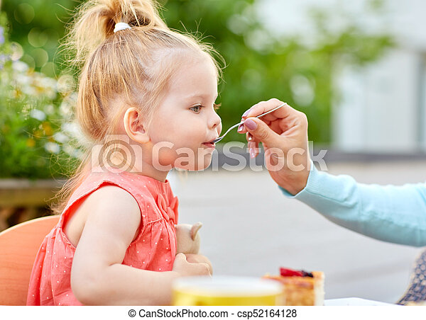 mother hand with spoon feeding daughter at cafe - csp52164128
