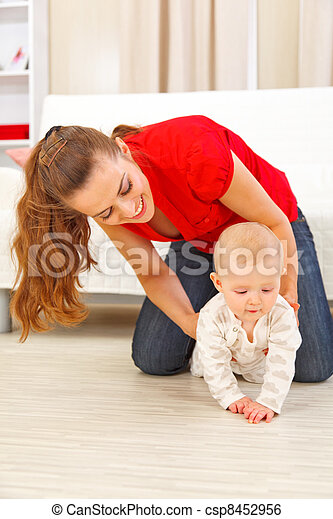 Mother helping cheerful baby learn to creep - csp8452956
